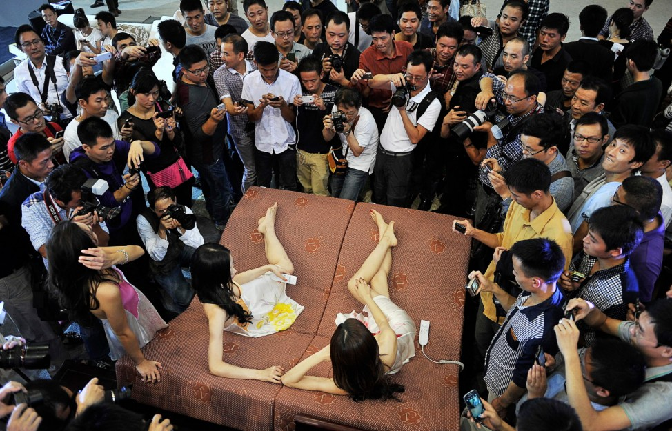 Visitors and journalists take pictures of models, who were promoting mattresses by lying on it, at an automobile exhibition in Hefei