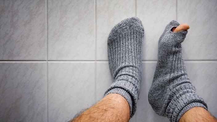 Mann mit Löchern in den Socken