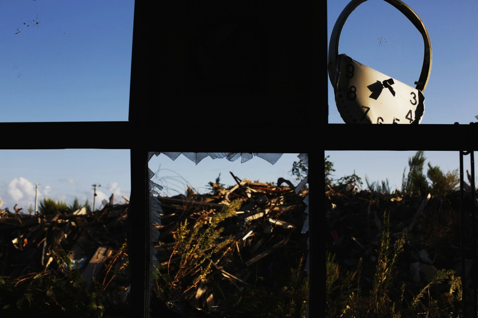 A twisted clock, spiders webs and debris are seen from inside a damaged primary school at the tsunami destroyed coastal area of the evacuated town of Namie