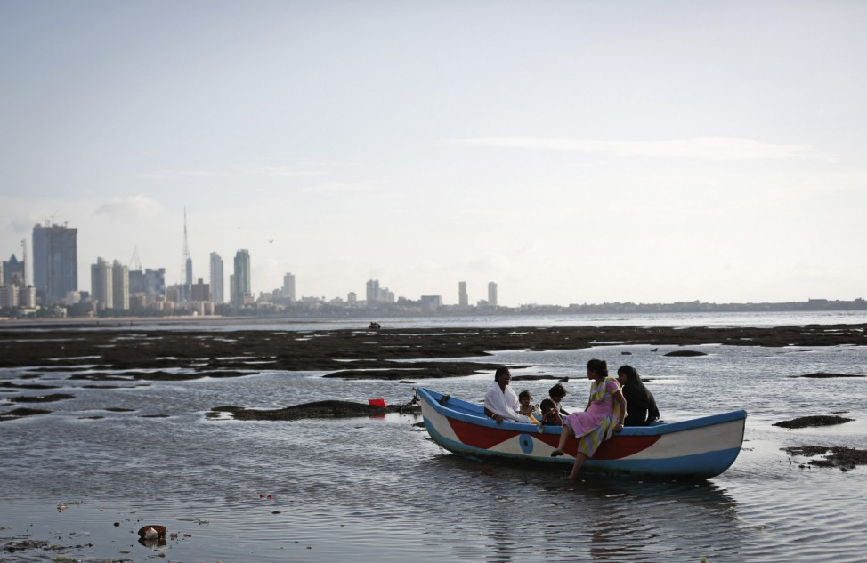 A family sits in an anchored boat in low waters in the Arabian Sea, off the coast of Mumbai