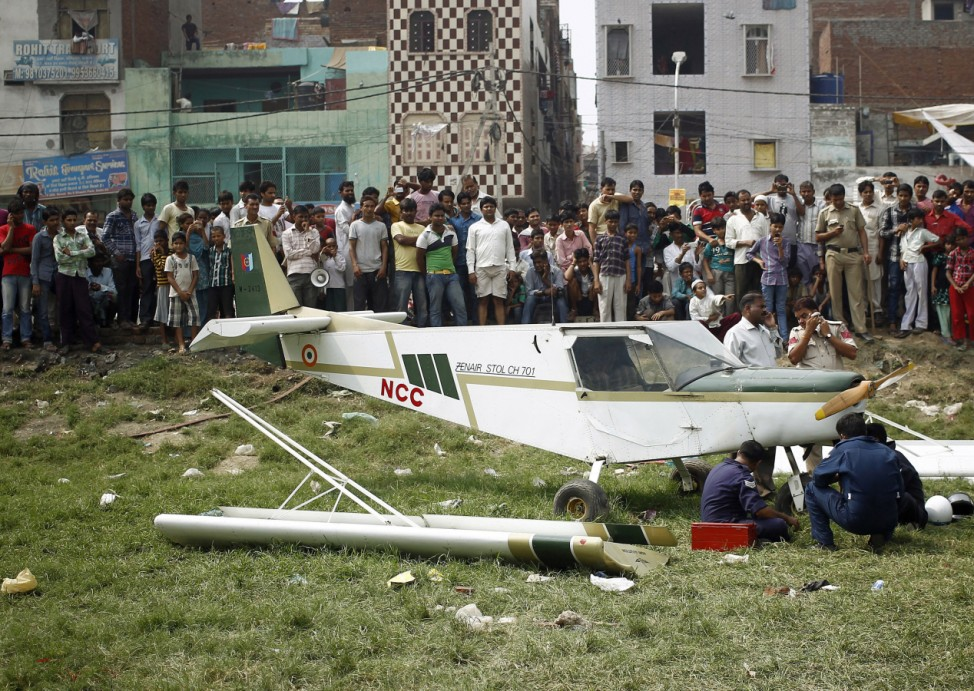 Indian Air Force personnel examine a damaged two-seater Microlight aircraft after it made an emergency landing in a park at New Delhi