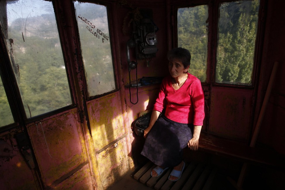 A conductor sits inside a 60-year-old cable car in the town of Chiatura