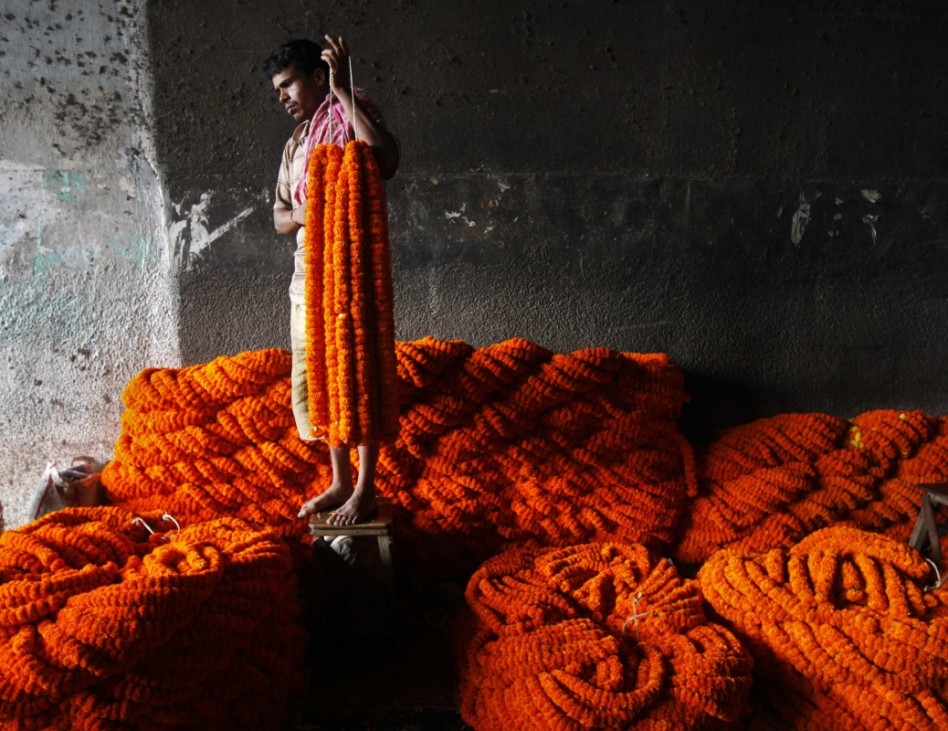 A vendor holds garlands of marigold flowers as he waits for customers at a wholesale flower market ahead of Durga Puja festival in Kolkata