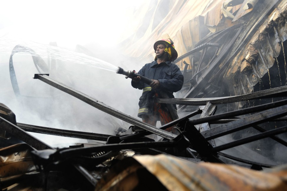 A firefighter tries to control a fire in a garment factory in the Bangladeshi town of Gazipur