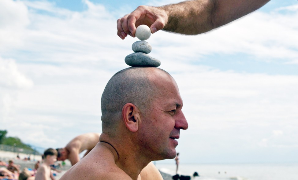 Engineer Yuri erects a stone pyramid on the head of his acquaintance and colleague Alexander as they rest on the beach in the Adler district of Sochi