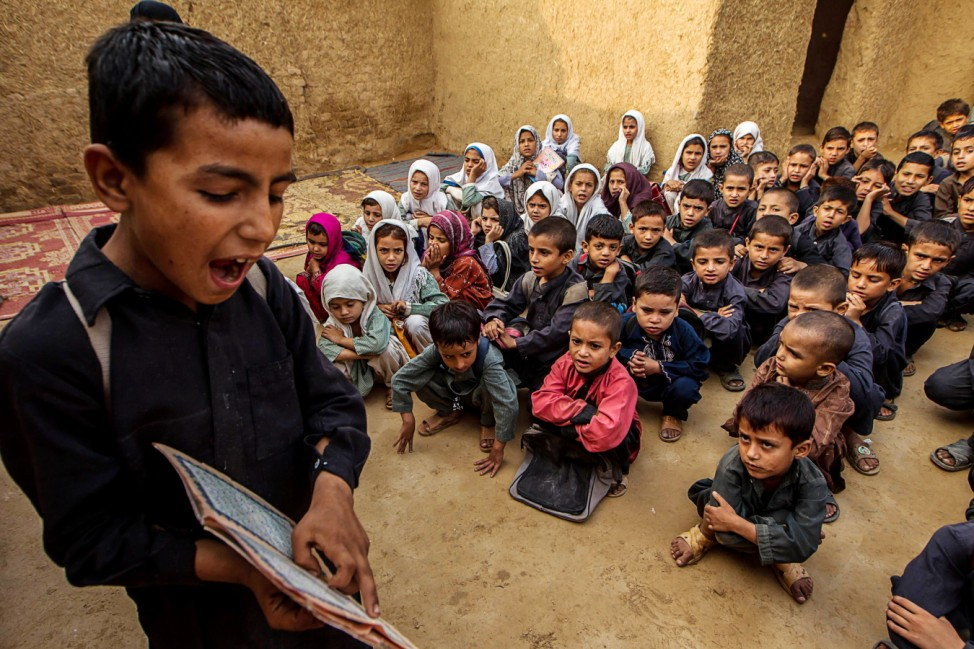 A boy recites from a book during a lesson at a school in a slum on the outskirts of Islamabad