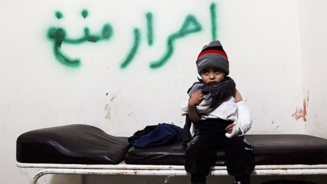 A wounded child sits on a stretcher as he is treated in a temporary medical center after he was injured during a shelling by forces loyal to President Bashar al Assad, in Aleppo
