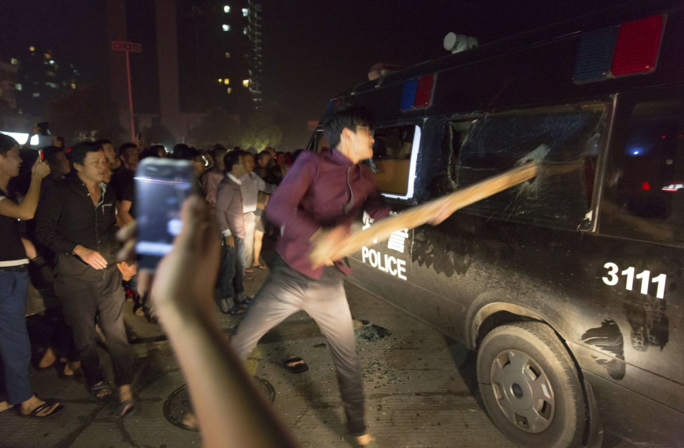 A man breaks the window of a police van with a wooden plank during a protest in Yuyao, Zhejiang province