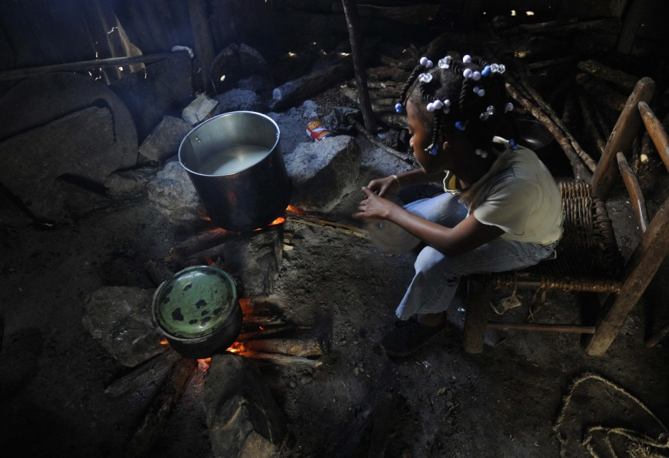 Maxileidy Louis watches cornmeal cook for breakfast at her family's home in La Loma