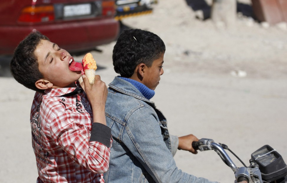 A boy eats ice cream while riding on the back of a motorcycle beside a market, ahead of the upcoming Muslim Eid al-Adha holiday, in Raqqa countryside