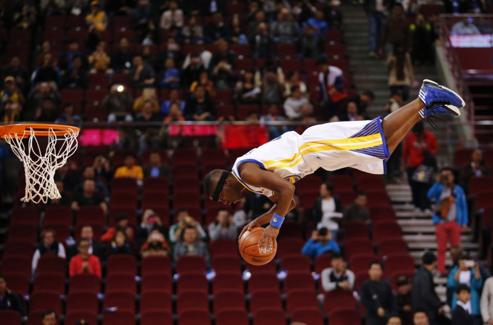 A member of the Flying Dubs, an acrobatic dunk team of the Golden State Warriors, performs before their NBA Global Game against the Los Angeles Lakers in Beijing