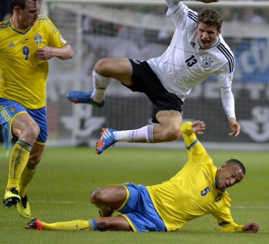 Germany's Muller jumps over Sweden's Olsson during their 2014 World Cup qualifying soccer match in Stockholm