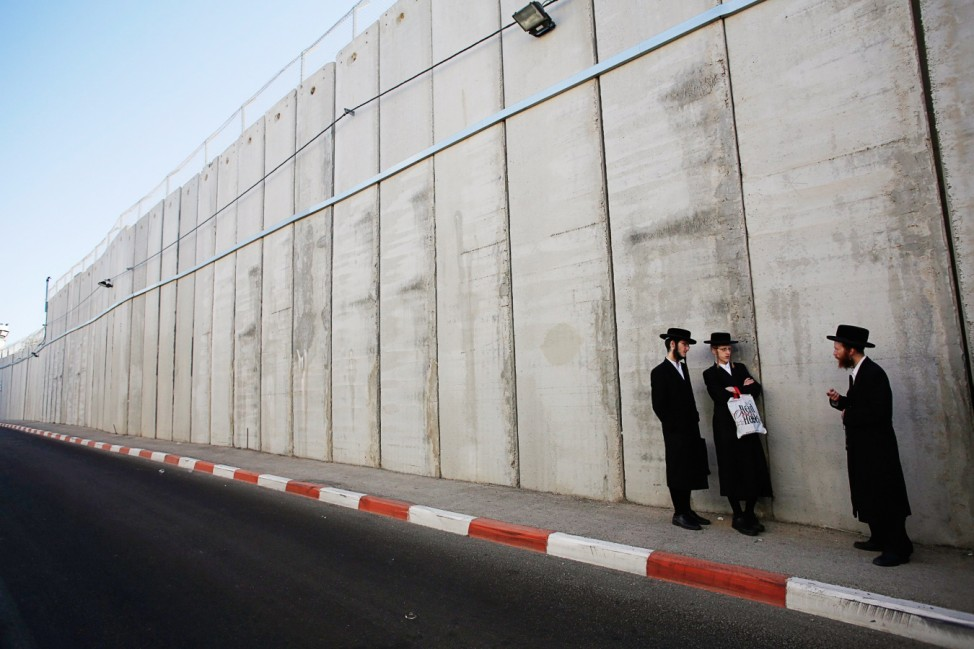 Ultra-Orthodox Jewish men wait for a bus after visiting Rachel's Tomb in Bethlehem