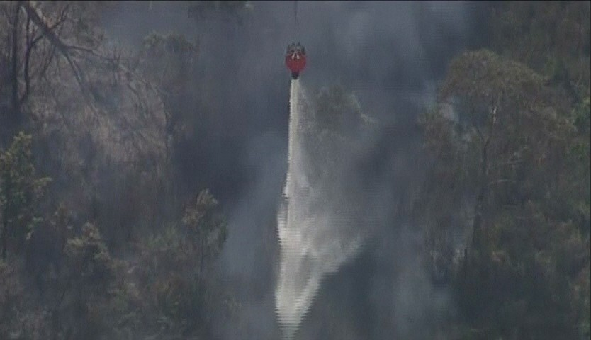 Still frame from video provided by Seven Network Australia shows a helicopter releasing water over bushfires in Lithgow, New South Wales