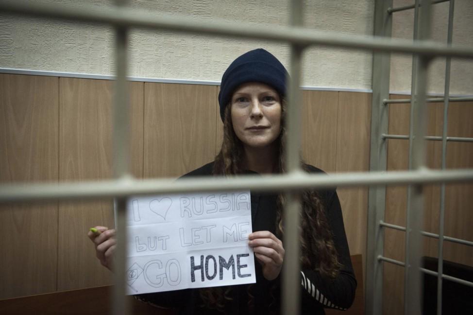 Greenpeace International activist Alminhana Maciel of Brazil holds a sign as she attends a bail hearing at a court in Murmansk
