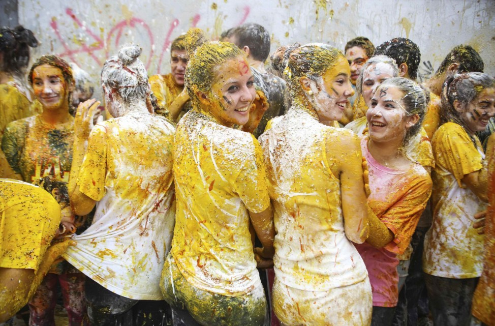 Faculty of medicine first year students are seen after seniors sprayed them with different types of sauces, liquids, flour and eggs as part of an annual tradition in Granada