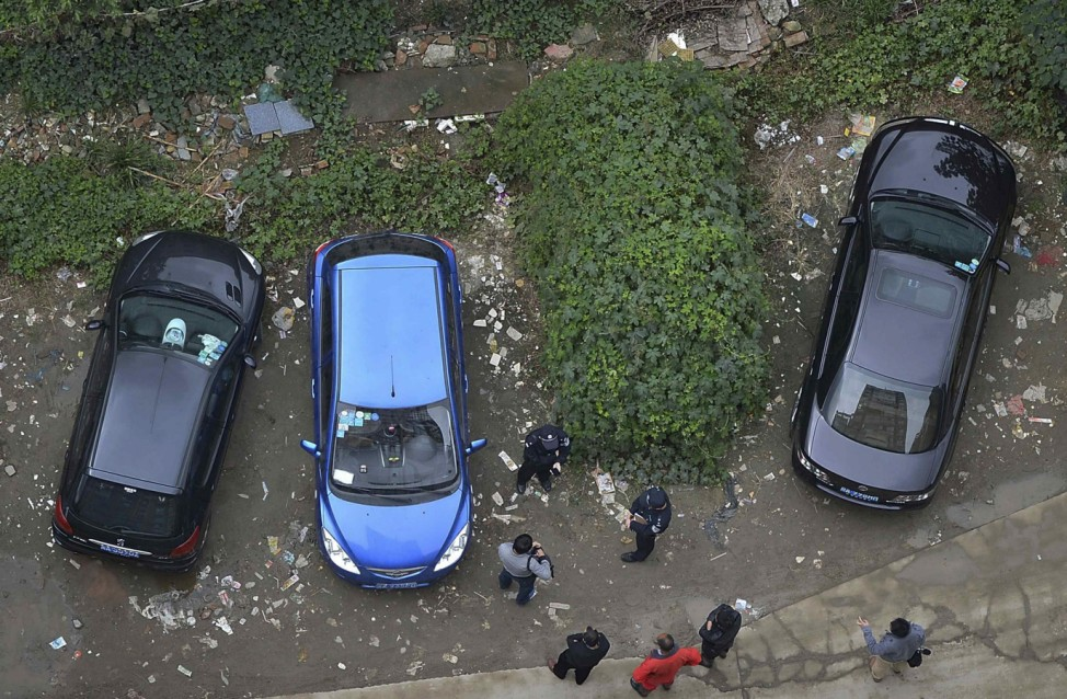 Police and bystanders look at a car which is covered with vegetation after it was left parked at a neighbourhood for more than a year, in Chengdu