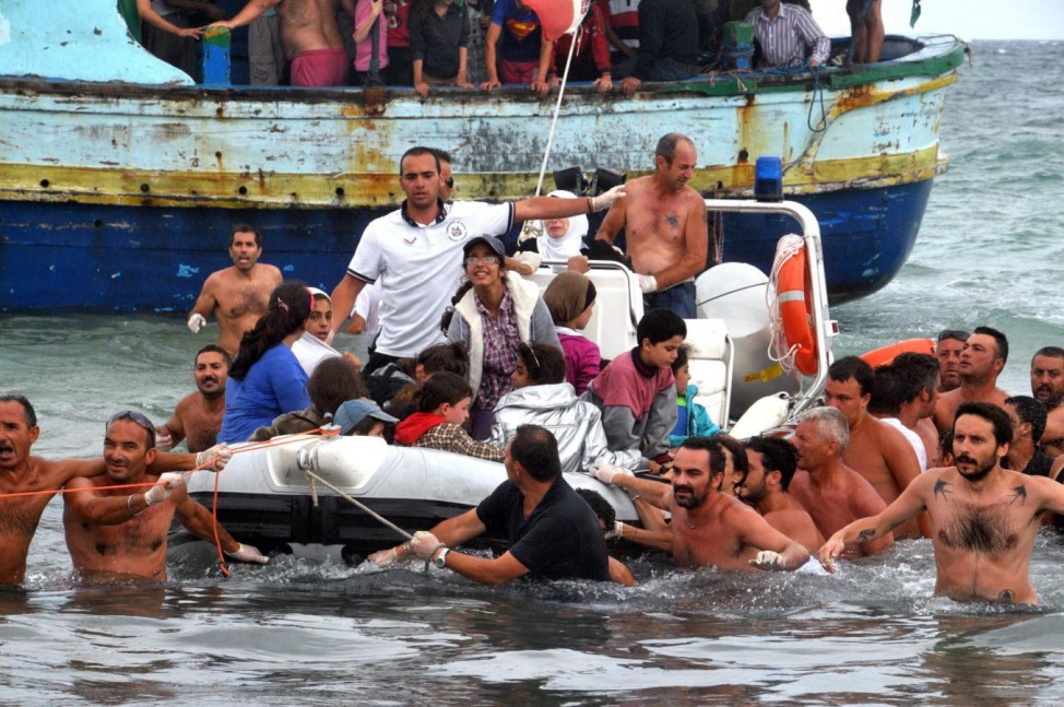 Beach goers and Italian coastguard rescue around 160 migrants