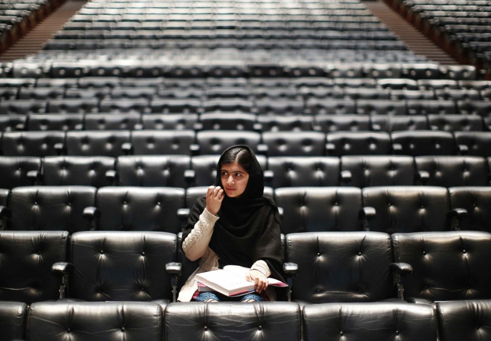 Pakistani teenage activist Yousafzai signs a copy of her book before an event launching her memoir 'I Am Malala' in London