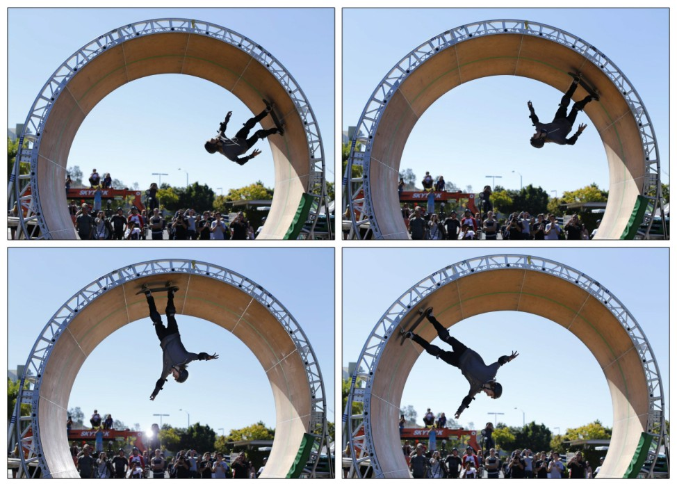 Skateboarder Aaron 'Jaws' Homoki  of Phoenix, Arizona manages to stay on his board as he completes his attempt to ride a 15 foot high skateboard loop in Vista, California