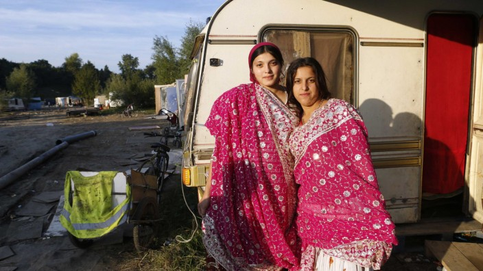 Teenage Roma sisters, Mailat and Borcha Sonita, pose in front of a caravan in an illegal camp in Croix