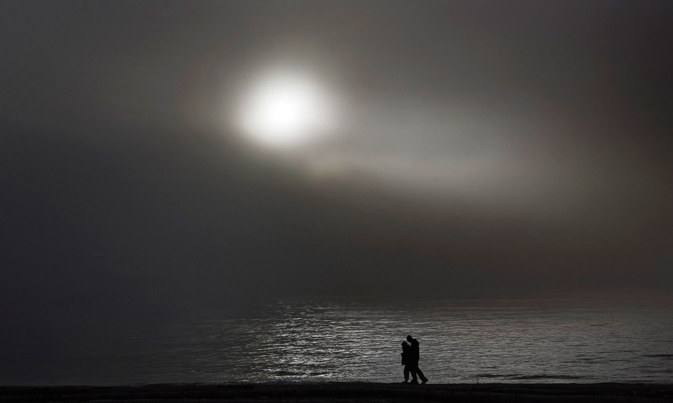 A couple takes a walk as the sun breaks through a fog along the waterfront in West Vancouver