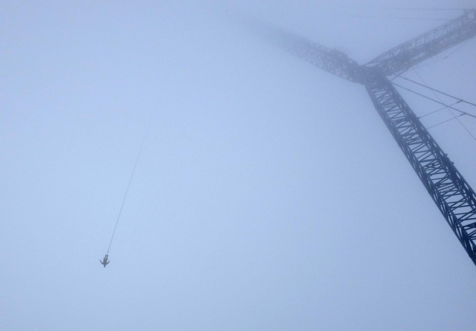 A member of Austrian special forces is suspended from one of highest bungee jump cranes in world in Vienna