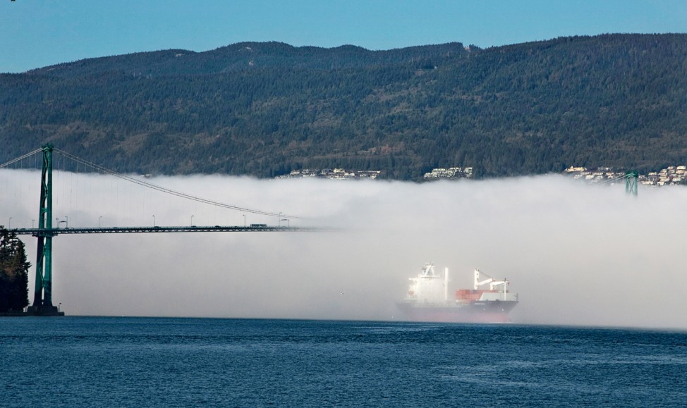 A ship emerges from a fog bank as it enters the inner harbour under the Lions Gate Bridge in Vancouver