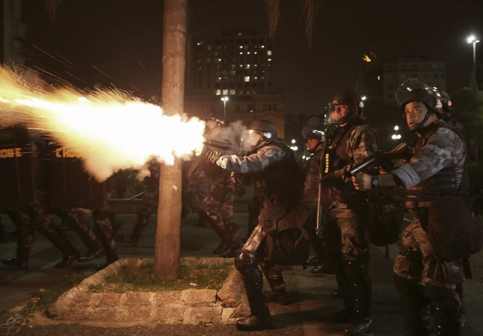 Military police fire tear gas at demonstrators from the group called Black Bloc, during a protest against bad conditions of public transport, in Sao Paulo