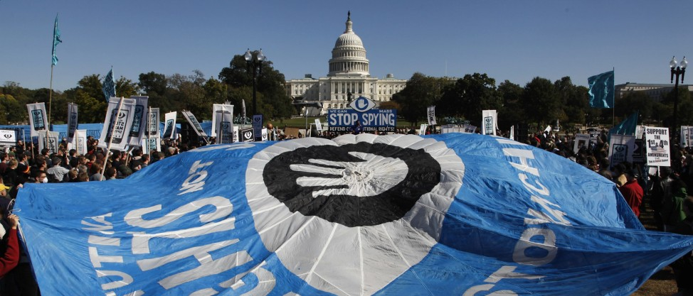 Demonstrators hold a parachute as they protest during the 'Stop Watching Us: A Rally Against Mass Surveillance' near the U.S. Capitol in Washington