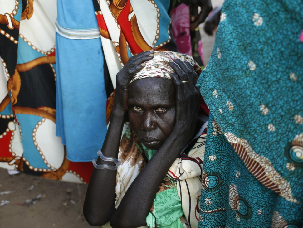 A women waits to vote in front of a polling station located in a school during a referendum in the town of Abyei
