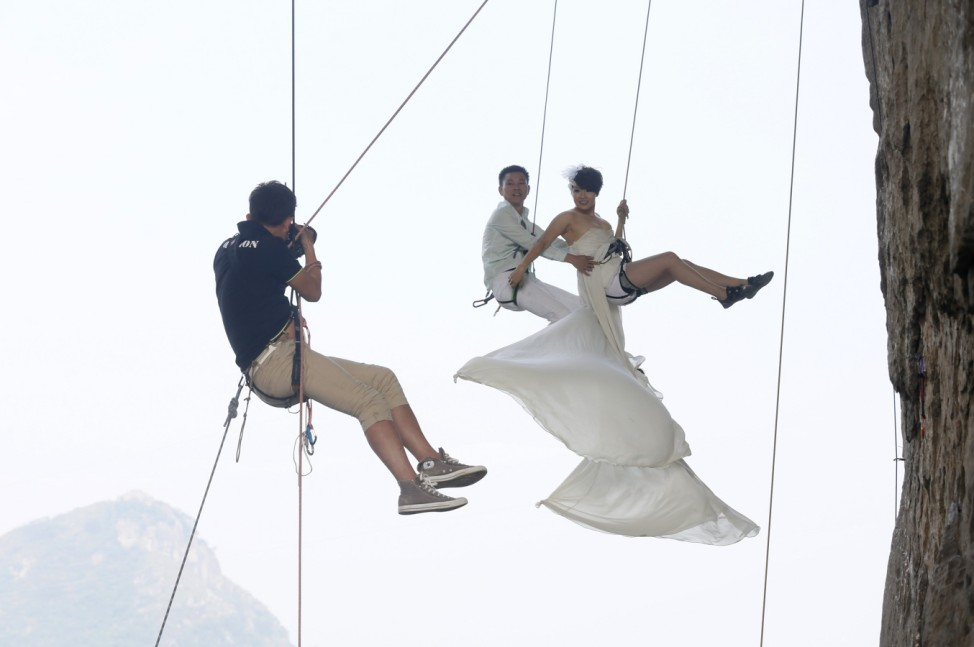 A photographer takes pictures of Fang in a wedding gown next to her husband as they hang from a cliff during a rock climbing exercise in Liuzhou