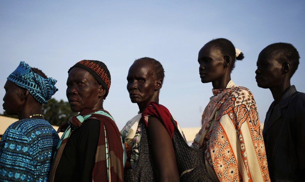 Women wait to vote in front of a polling station located at a school during a referendum in the town of Abyei