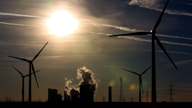 Welle von Kraftwerksabschaltungen: Windräder vor RWE-Kraftwerk Niederaußem: Der Energiekonzern warnt vor Blackouts.