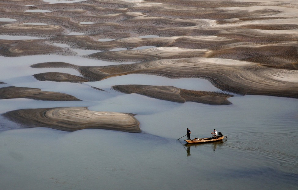 Two men row a boat past a partially dried-up riverbed on a section of the Yangtze River in Jiujiang