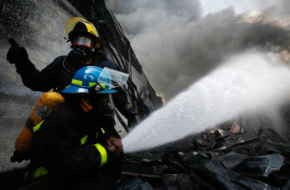 Firefighters work to extinguish a fire at a plastic factory in San Salvador