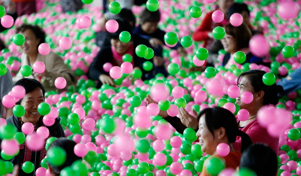 Participants play in a swimming pool filled with pink and green plastic balls during a Guinness World Records attempt of the Largest Ball Pit as part of the 'Pink October' campaign at Kerry Hotel in Pudong, Shanghai