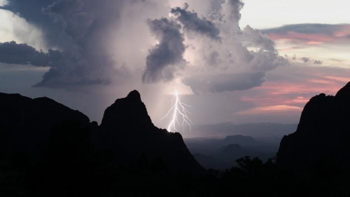 Neue Erkenntnisse zu Gewittern: Über einen Höhenzug in Texas schießt eine Gewitterwolke Blitze in das Gestein. Sie können die Form der Berge auf Dauer deutlich verändern.