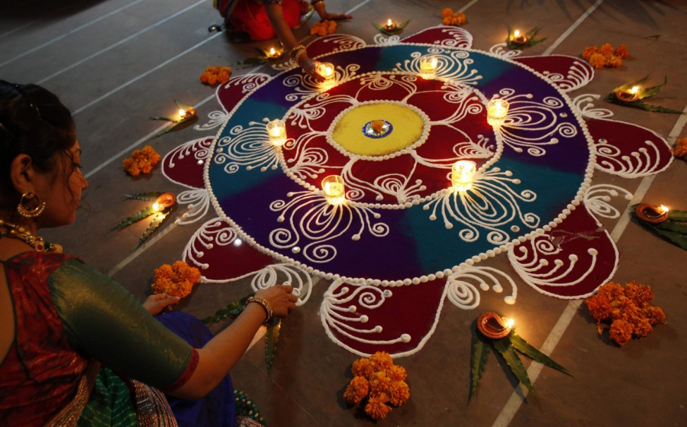 Hindu women arrange oil lamps and flowers around a Rangoli during the celebrations ahead of the Hindu festival of Diwali in Ahmedabad