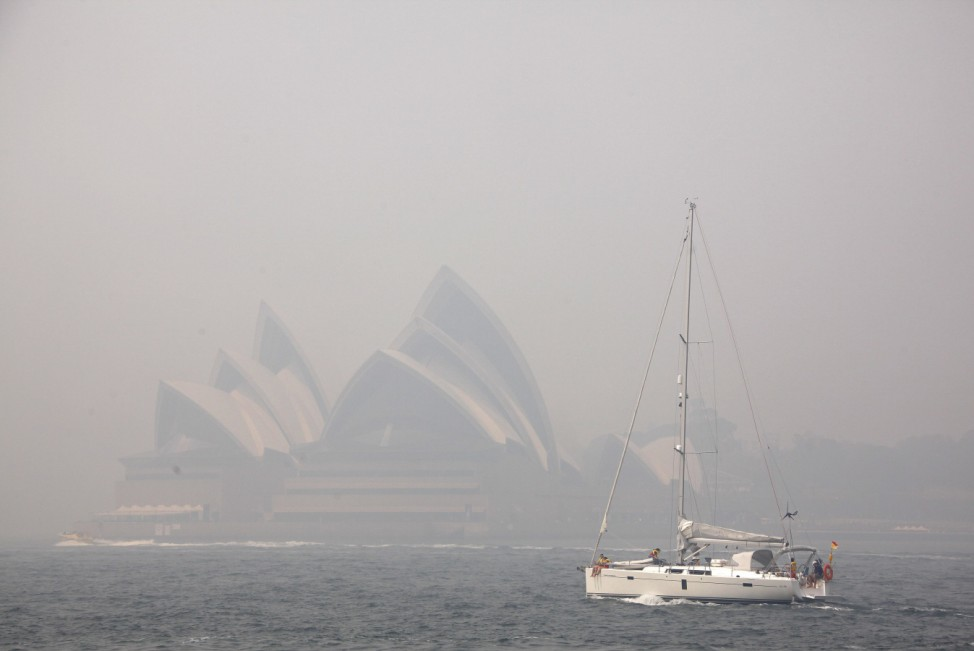 A sailing boat passes the Sydney Opera House as smoke from bushfires blankets the city