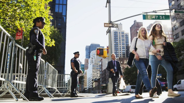 New York Police Department officers stand in front of barriers blocking street, in preparation for United Nations General Assembly, in New York