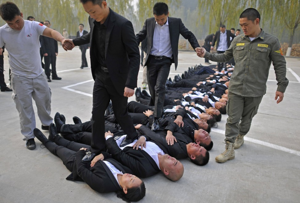 Trainees walk over the bodies of their fellow trainees during the Tianjiao Special Guard/Security Consultant Ltd. bodyguard training camp in Beijing