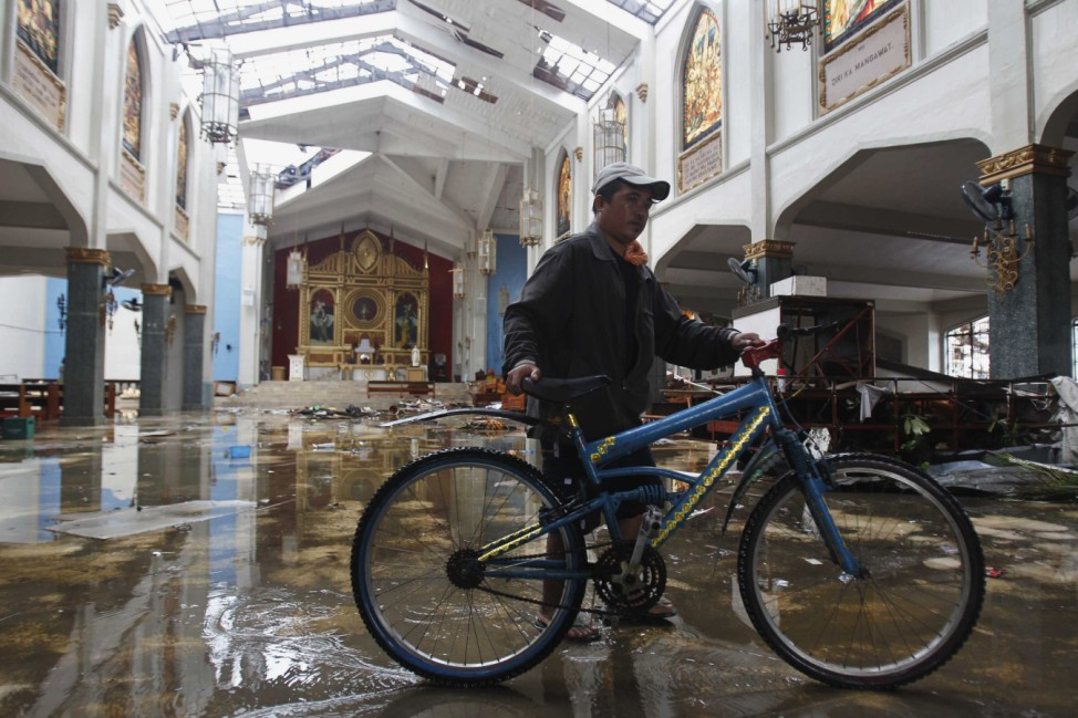 A man with bicycle enters a Catholic church which was damaged after super Typhoon Haiyan battered Tacloban city