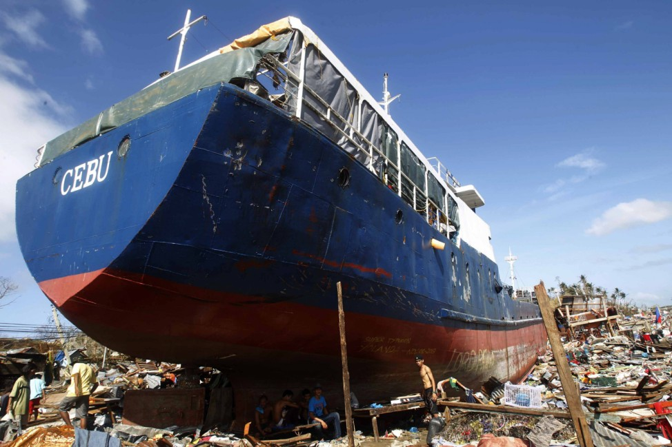 Residents rest under a cargo ship after super typhoon Haiyan hit Anibong town, Tacloban