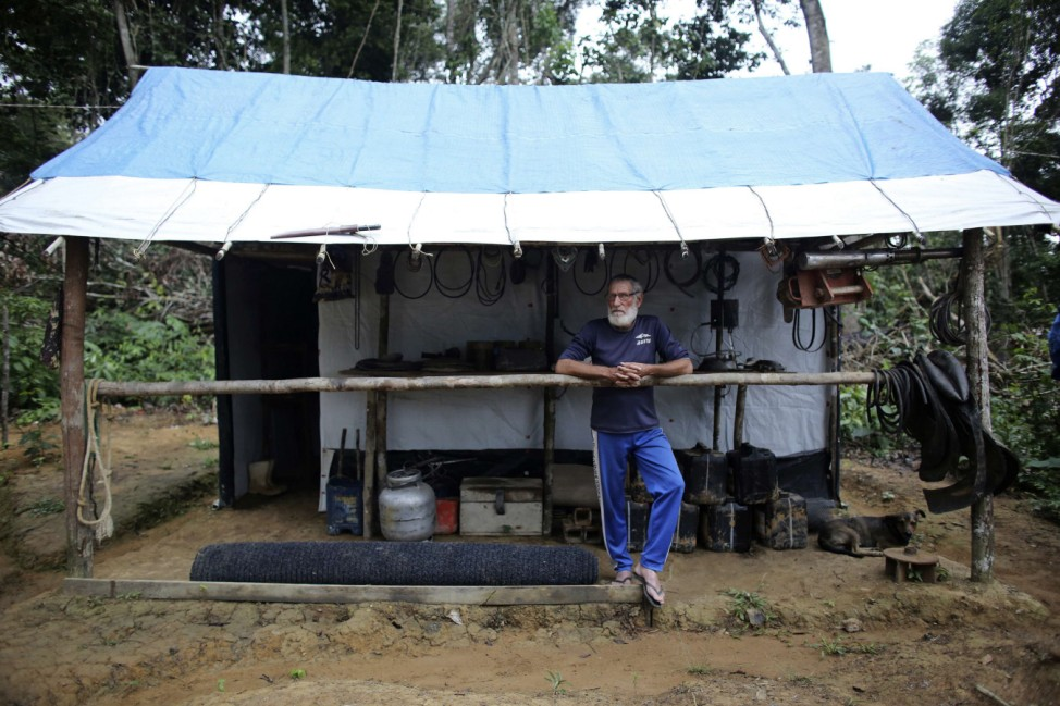 A man stands in front of his shack next to a mine in the Amazon rainforest near the city of Morais Almeida
