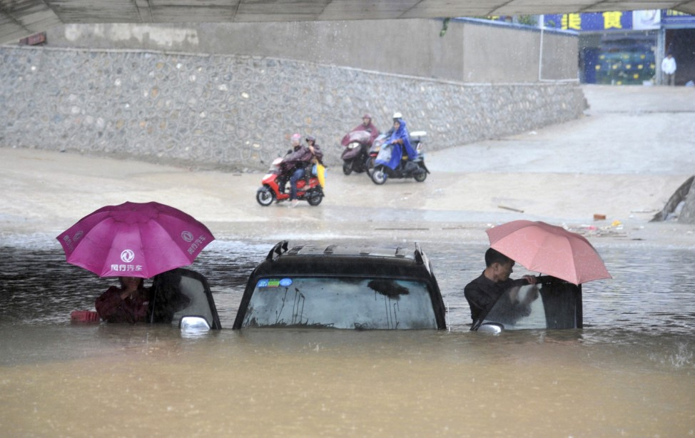 People get out of a stranded car at a flooded underpass amid heavy rainfalls under the influence of Typhoon Haiyan, in Nanning