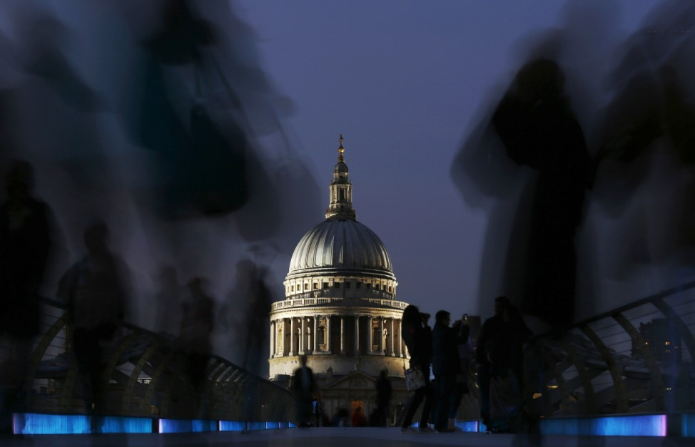 St Paul's Cathedral is illuminated as people walk across the Millennium Bridge during the evening rush hour in London