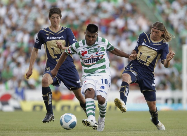 Santos' Luduena drives ball past Pumas' Augusto and Palacios during their Mexican championship quarter-final soccer match in Torreon