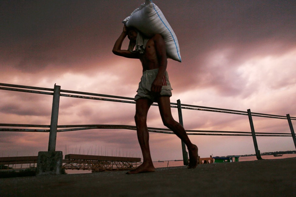 A man carries a sack of rice from a boat on the banks of the Yangon river in Yangon