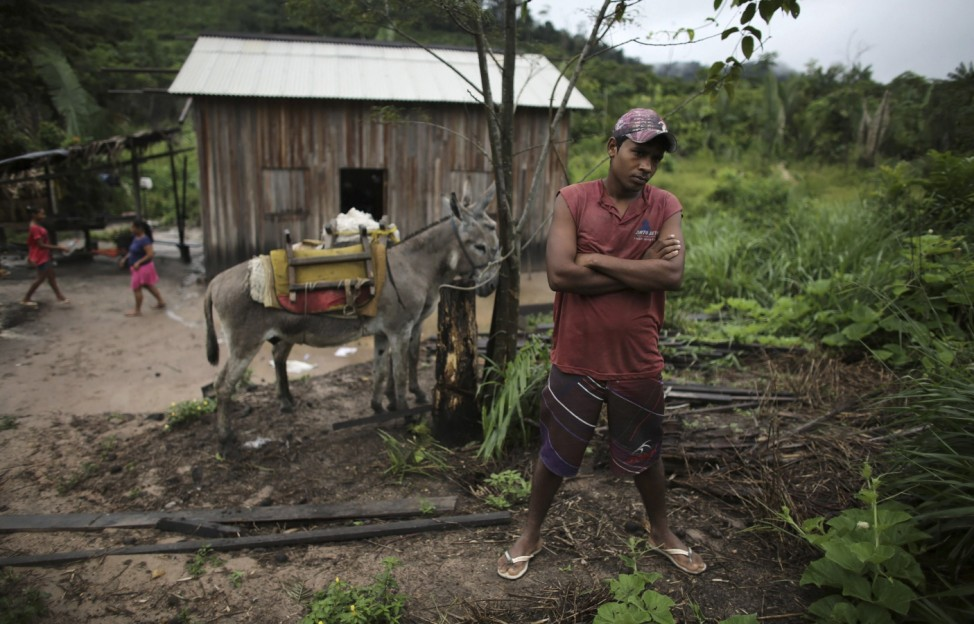 A man stands in front of his home in the Amazon rainforest near the city of Uruara